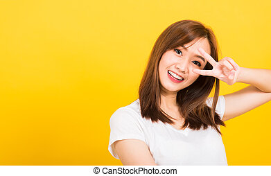 woman teen smile standing wear t-shirt showing finger making v-sign symbol near eye
