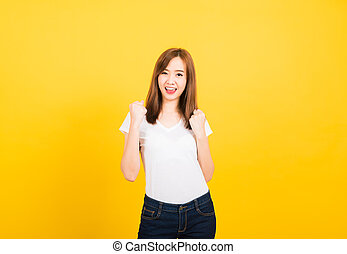 woman teen standing wear t-shirt makes raised fists up celebrating her success
