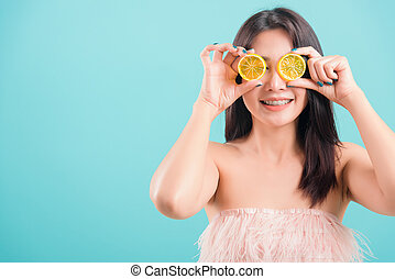woman standing smile holding a piece of orange in front of her eye
