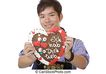 Asian holding Oktoberfest heart in camera and smiles - Asian...