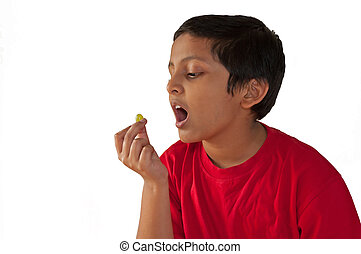 Asian, Indian, Bengali young boy eating grape, open mouth,isolated,white background