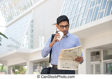 asian indian business man with coffee and papers