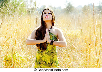 Asian indian woman praying hands in golden field with green ...