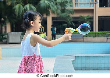 Asian kid blowing bubble