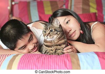 Asian kid lay on his bedroom with cat
