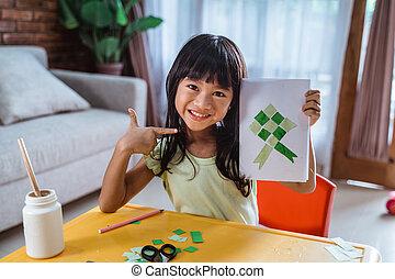 asian kid making eid mubarak card