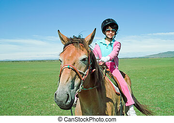Asian kid riding horse - An Asian kid riding horse in the...