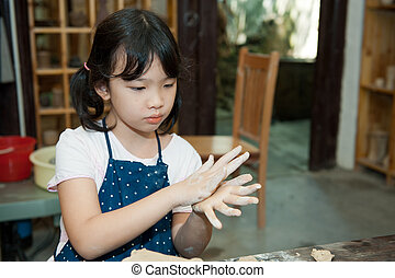 Asian kid shaping pottery