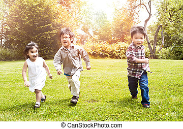 Asian kids running in park - A shot of three Asian kids ...