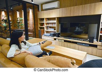 asian kobieta, używając, niejaki, zdalne sterowanie, żeby obrócić się, na, telewizja, z, okienko osłaniają