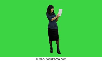 Asian lady having video chat using a tablet on a Green Screen, Chroma Key