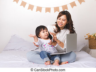 Asian lady in classic suitvworking on laptop at home with her baby girl chatting with father.