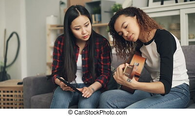 Asian lady is using laptop to teach her African-American friend to play the guitar learning at home together. Girls are talking and laughing enjoying activity.