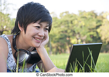 Asian lady using computer in a field