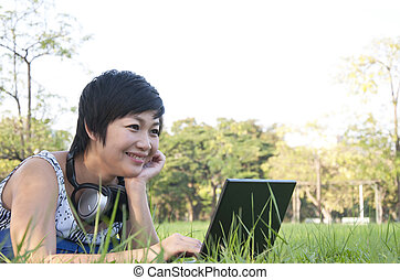 Asian lady using computer in a park