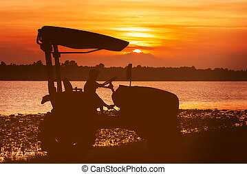 asian little boy driver tractor on river sunset background