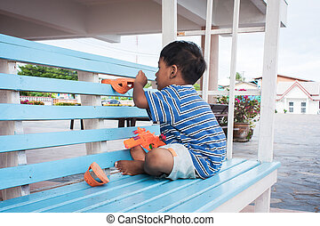 asian little boy playing on the chair