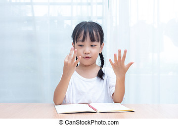 Asian little Chinese Girl doing mathematics by counting fingers