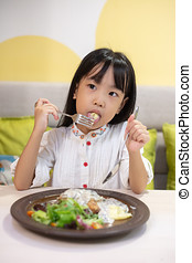 Asian Little Chinese Girl Eating Western Food at restaurant