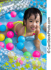Asian Little Chinese Girl Playing in an Inflatable Rubber Swimming Pool
