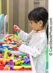 Asian Little Chinese Girl playing puzzle