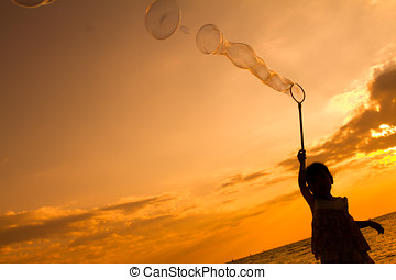 Asian Little Chinese Girl Playing Soap Bubbles on the Beach