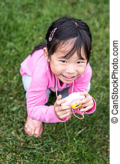 Asian little girl holding a plastic camera toy