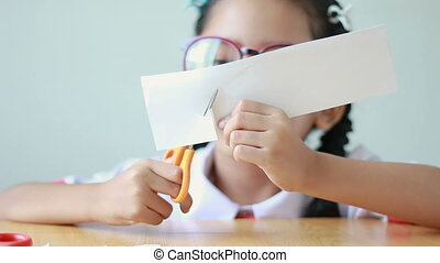 Asian little girl in Thai kindergarten student uniform using scissor to cut the white paper on wooden table select focus on hands