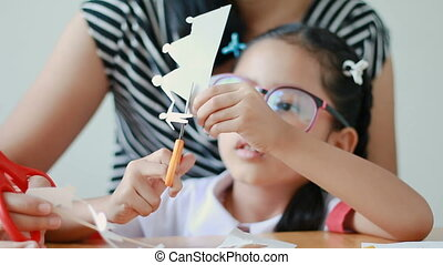 Asian little girl in Thai kindergarten student uniform and her mother using scissor to cut the white paper making family shape father mother son and daughter on wooden table select focus on hands