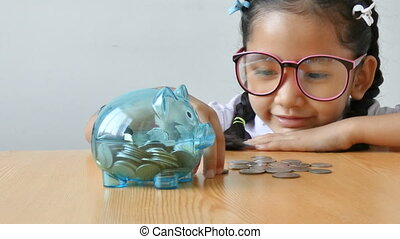 Asian little girl in Thai kindergarten student uniform putting money coin into clear piggy bank on wooden table metaphor money saving for education concept shallow depth of field select focus on pig