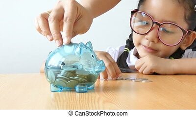 Asian little girl in Thai kindergarten student uniform putting money coin into clear piggy bank on wooden table metaphor money saving for education concept