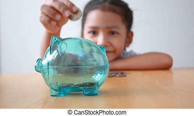 Asian little girl in Thai kindergarten student uniform putting money coin into clear piggy bank select focus on pig saving money for education concept with ambient sound