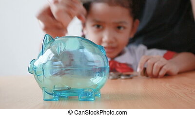 Asian little girl in Thai kindergarten student uniform putting money coin into clear piggy bank select focus on pig saving money for education concept