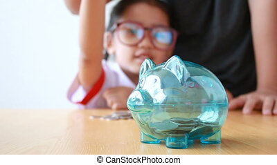 Asian little girl in Thai kindergarten student uniform putting money coin into clear piggy bank with hands of mother select focus on pig saving money for education concept with ambient sound