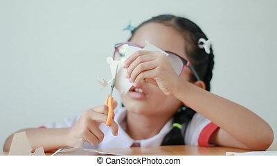 Asian little girl in Thai kindergarten student uniform using...