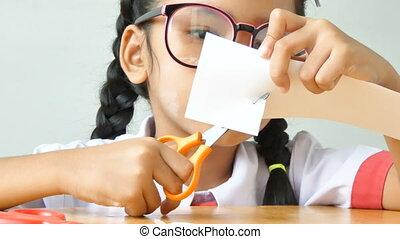 Asian little girl in Thai kindergarten student uniform using scissor to cut the white paper on wooden table