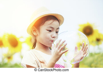 Asian little girl is blowing a soap bubbles in sunflower garden