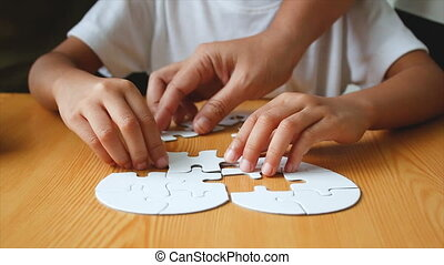 Asian little girl playing jigsaw puzzle select focus on hand...