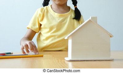 Asian little girl putting money coin into clear house bank metaphor saving money for buy the house and real estate concept