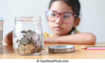 Asian little girl putting the coin into a clear glass jar on table metaphor saving money concept with sound select focus on jar