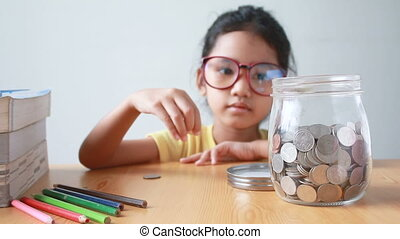 Asian little girl putting the coin into a clear glass jar with the book on table metaphor saving money for education concept with sound select focus on jar