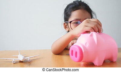 Asian little girl putting the coin into a pink piggy bank with air plane metaphor saving money for travel and transport concept