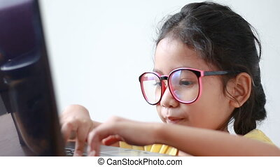 Asian little girl using laptop computer with sound