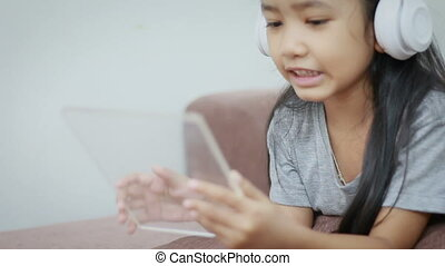 Asian little girl using white wireless headphone and clear pad for futuristic technology mobile application concept
