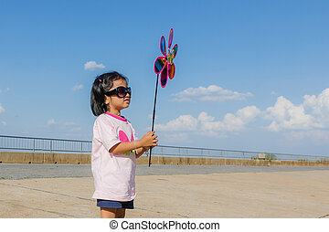 Asian little girl with wind turbine toy in hands