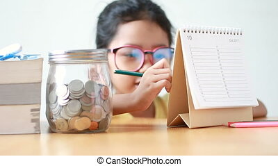 Asian little girl writing on calendar with glass jar on table metaphor saving money concept