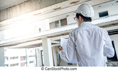 Asian male engineer checking blueprints at construction site