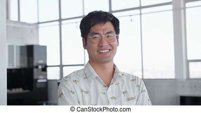 Asian male executive standing with arms crossed in modern office 4k
