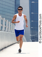 Asian male runner - Asian male jogging with skyscraper in...