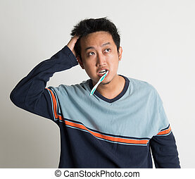 Asian male scratching head and looking up while brushing teeth